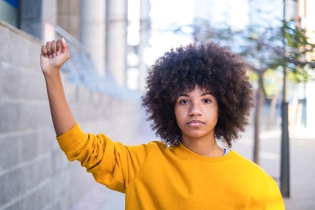 Concept black lives matter. une jeune femme africaine ou américaine sérieuse avec son bras vers le haut avec la main étroite regardant la caméra.