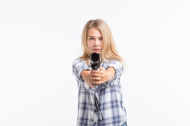 Concept de blague, de photographie et d'humour - jeune femme blonde avec appareil photo rétro comme une arme à feu sur fond blanc.