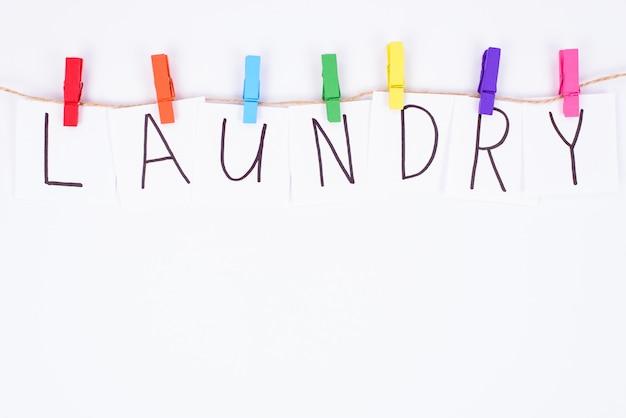 Concept de blanchisserie. haut au-dessus de la vue grand angle de la lettre et des pinces à linge colorées accroché sur un mur blanc isolé de la corde