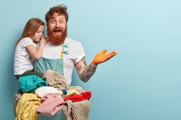 Concept de blanchisserie et de ménage. homme rousse ravi avec une barbe épaisse