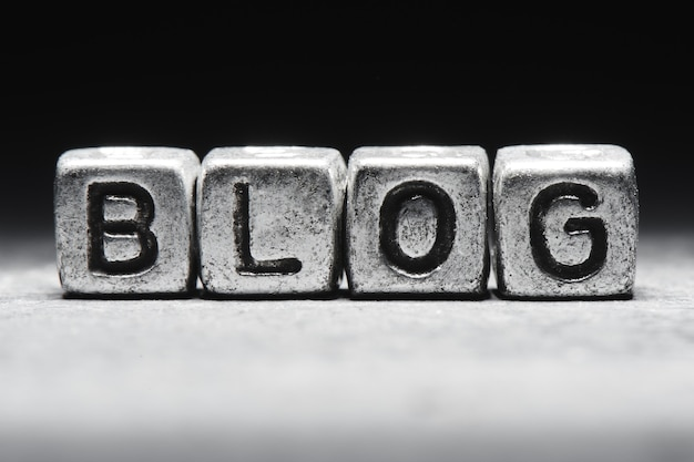Concept de blog. l'inscription sur des cubes 3d métalliques isolés sur fond noir, style grunge