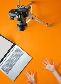 Concept de blogueur en ligne. réviseur d'émoticônes. les mains des femmes montrent un blog émotionnel avec ñ amera sur trépied, ordinateur portable sur fond orange. minimalisme.