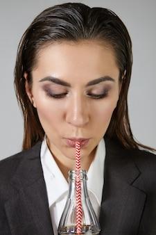 Concept de boisson, repos, personnes et mode de vie. élégante jeune femme d'affaires autoritaire brune aux yeux charbonneux maquillage et cheveux mouillés vêtus d'élégants vêtements formels surdimensionnés, ayant une boisson alcoolisée