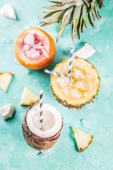 Concept de boisson de vacances d'été, définir divers cocktails tropicaux ou jus à l'ananas, au pamplemousse et à la noix de coco avec de la glace, table en béton bleu clair