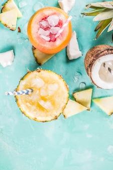 Concept de boisson de vacances d'été, définissez divers cocktails tropicaux ou jus à l'ananas, au pamplemousse et à la noix de coco avec de la glace, du béton bleu clair