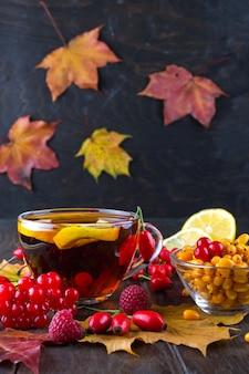 Concept de boissons saines d'automne. tasse de thé avec des baies d'argousier, de la viorne, du cynorrhodon, du sorbier et des feuilles d'automne. boire avec de la vitamine c