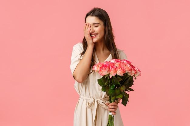 Concept de bonheur, d'amour et de relation, femme se sentant chérie et appréciée, jolie fille brune en robe élégante, tenant des roses, bouquet de fleurs et souriant, riant timide, rose