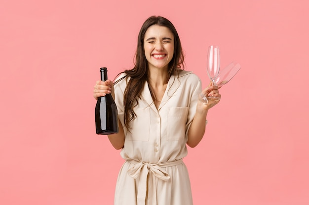 Concept de bonheur, de célébration et de félicitations. charmante et excitée, extatique femme caucasienne en robe, fermer les yeux et sourire joyeusement, bouteille de champagne ouverte et boire ensemble