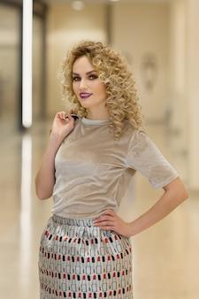 Concept de bonheur, de consommation, de vente et de personnes. jeune femme souriante avec des sacs à provisions dans le centre commercial.