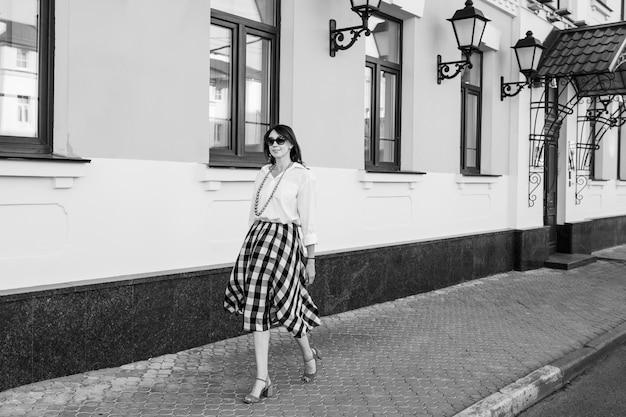 Concept de bonheur - femme heureuse s'amuser sur la rue de la ville. femme fashion à lunettes de soleil marche dans la rue sur des talons hauts. image en noir et blanc.