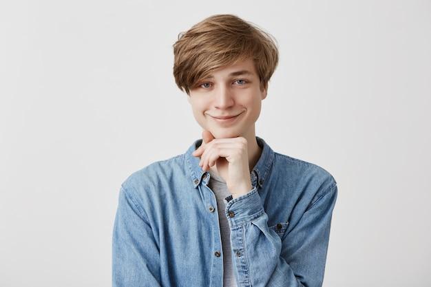Concept de bonheur, de positivité et de personnes. sourire heureux jeune homme blond en chemise en jean, garde la main sous le menton, se réjouit les week-ends à venir, a de grands projets de passer du temps avec des amis