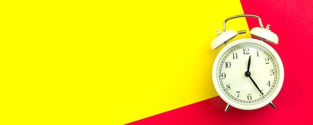 Concept de bonjour, bannière avec réveil blanc sur fond coloré et lumineux, espace de copie et photo vue de dessus