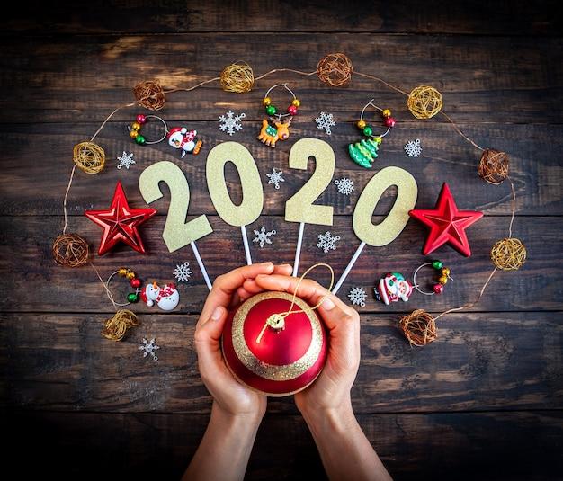 Concept de bonne année 2020 avec des décorations de noël et des mains féminines tenant babiole sur fond en bois