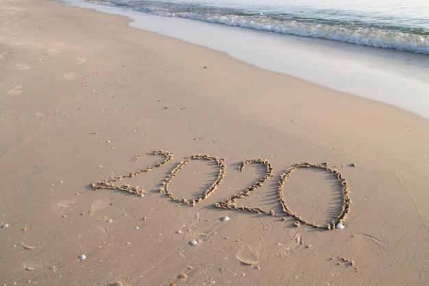 Concept de bonne année 2020 avec lettre de sable sur l'espace de copie de plage