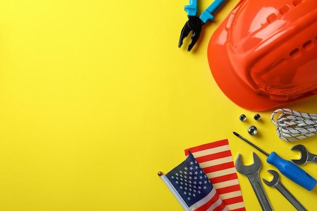 Concept de bonne fête du travail avec différents accessoires sur jaune