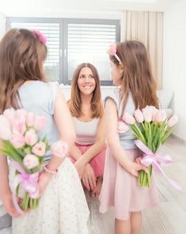 Concept de bonne fête des mères. jolies petites filles avec un bouquet de tulipes derrière le dos en cadeau à leur mère.