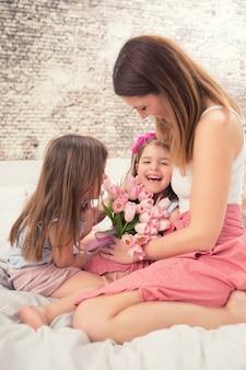 Concept de bonne fête des mères. maman avec deux jeunes filles jumelles mignonnes sur le lit dans la chambre et un bouquet de tulipes de fleurs.