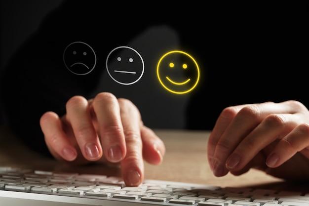 Concept de bonne humeur composé d'émoticônes et d'évaluations. la fille met une évaluation à l'aide du clavier.