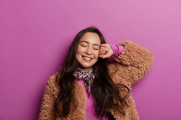 Concept de bonne humeur. jeune femme rêveuse détendue incline la tête, sourit doucement, vêtue de vêtements d'extérieur, garde les yeux fermés, isolée sur l'espace lilas