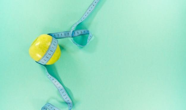Concept d'une bonne nutrition, ruban à mesurer avec apple sur turquoise