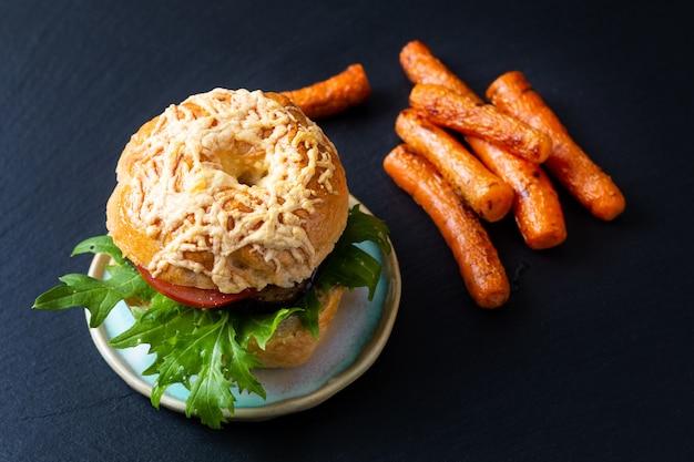 Concept de boulangerie alimentaire bagel bio fait maison sandwich végétarien roquette d'aubergines grillées et carottes rôties