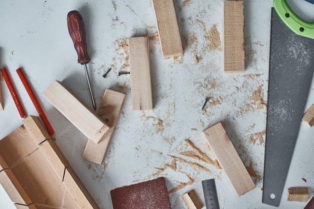 Concept de bricolage. table de travail avec des outils de menuisier et des planches de bois recadrées, vue de dessus.