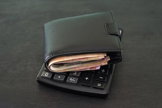 Concept de budget et d'argent. portefeuille plein d'argent avec une calculatrice sur un tableau noir.