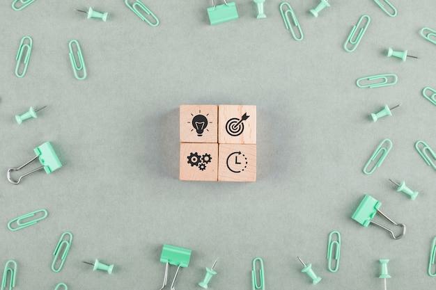 Concept de bureau d'affaires avec des blocs en bois avec des icônes, des trombones, des clips de reliure vue de dessus.