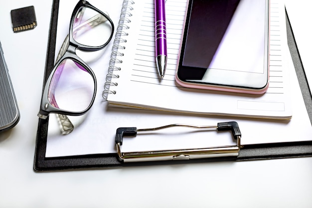 Concept de bureau et d'entreprise. articles sur le bureau d'un homme d'affaires. smartphone, tablette pour notes et verres d'un homme d'affaires.