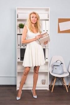 Concept de bureau, intérieur et personnes - jeune femme blonde a ouvert le portefeuille du photographe au bureau de