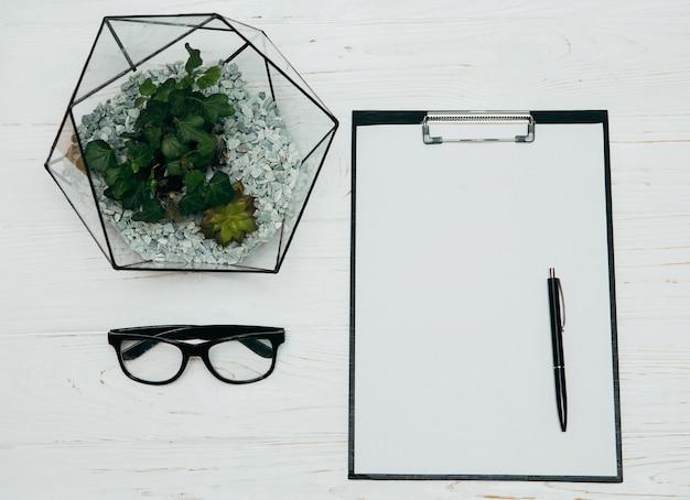 Concept de bureau. vase de florarium, bloc-notes et verres sur fond blanc.