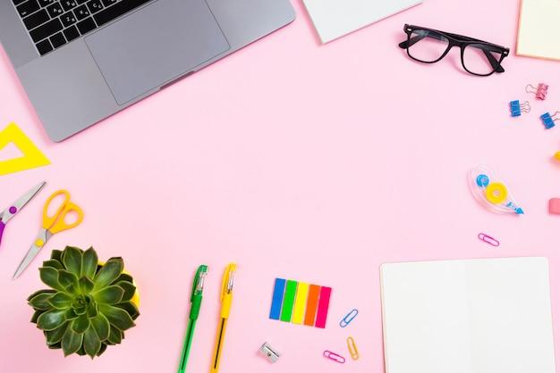 Concept de bureau vue de dessus avec fond rose