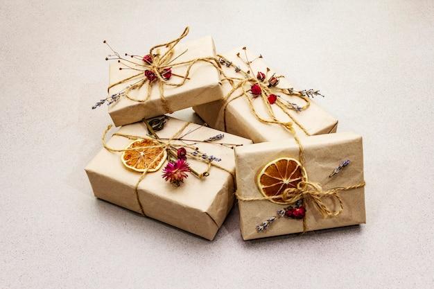 Concept de cadeau zéro déchet. emballage écologique pour la saint-valentin ou l'anniversaire. boîtes festives en papier kraft avec différentes décorations organiques.