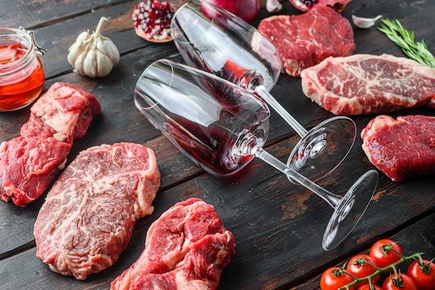 Concept de cadre de steaks de boeuf à la viande, avec différentes coupes de steak et deux verres à vin dans un cadre sur une vieille table en bois sombre vue latérale.
