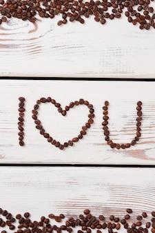 Concept de café d'amour. je t'aime fait de grains de café sur une surface en bois blanche.