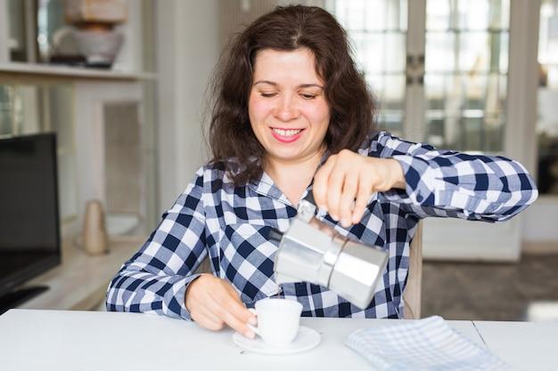 Concept de café, de boissons et de repas - jeune femme avec cafetière, verser le café dans la tasse.