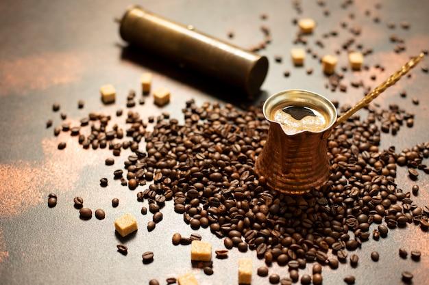 Concept de café turc. cafetière en cuivre (cezve), moulin à café vintage, grains de café et sucre sur un fond vintage sombre. fermer