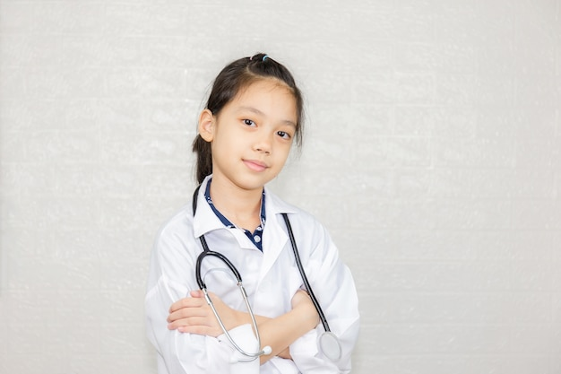 Concept de carrières de rêve, portrait d'enfant heureux en manteau de médecin avec arrière-plan flou stéthoscope