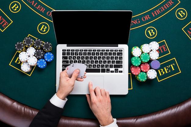 Concept de casino, de jeu en ligne, de technologie et de personnes - gros plan sur un joueur de poker avec des cartes à jouer