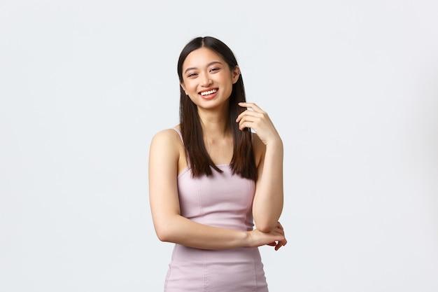 Concept de célébration, de beauté et de glamour. élégante fille asiatique en robe de soirée élégante, riant comme parler à la fête d'hôte