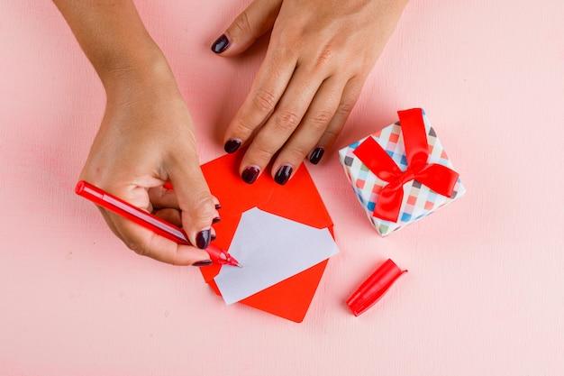 Concept de célébration avec boîte-cadeau sur table rose à plat. femme signant une carte de voeux.