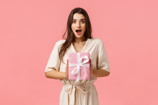 Concept de célébration, de bonheur et d'émotions. enthousiaste jeune femme recevoir un cadeau agréable, tenant un cadeau enveloppé, haletant, bouche ouverte et l'air fasciné, fond rose