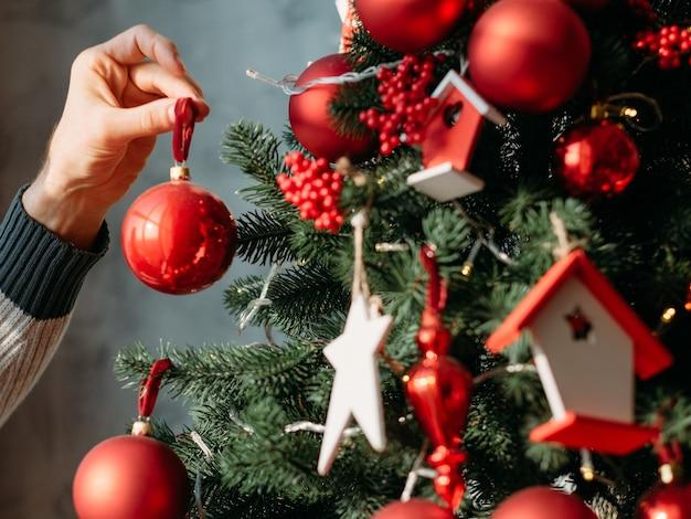 Concept de célébration du nouvel an. gros plan de la main de l'homme tenant l'ornement de boule rouge pour décorer le sapin vert.