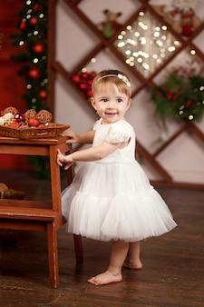 Concept de célébration du nouvel an et de noël. jolie petite fille en robe blanche jouant et étant heureuse de l'arbre de noël et des lumières. vacances d'hiver.