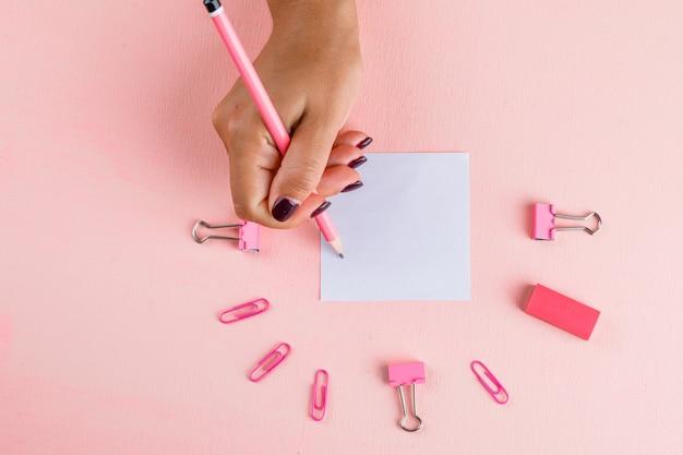 Concept de célébration avec du papier et des agrafes de reliure, gomme sur table rose à plat. femme écrivant sur pense-bête.
