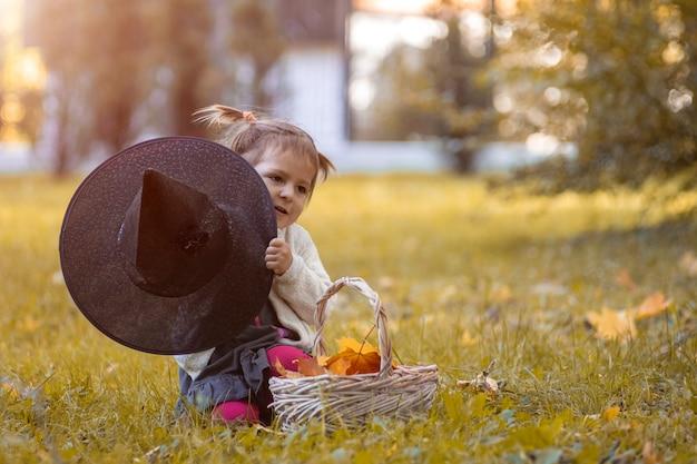Concept de célébration d'halloween. tout-petit mignon jouant et se cache derrière un chapeau de sorcière dans un parc en automne.
