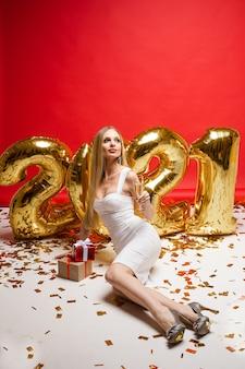 Concept de célébration de noël du nouvel an. belle femme, ballons en forme 2021, cadeaux, confettis dorés sur mur rouge.