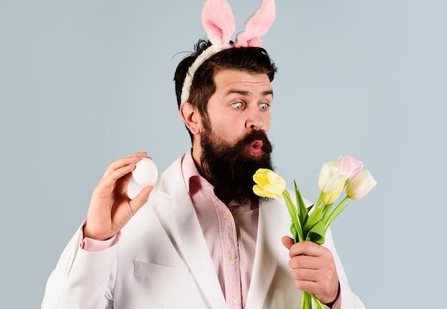 Concept de célébration de pâques. homme barbu surpris en costume avec oeuf et fleurs. chasse aux œufs.