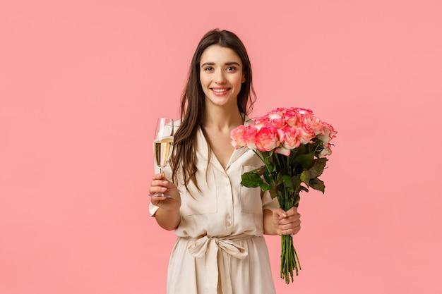 Concept de célébration, de romance et de relation. séduisante belle femme célébrant et faisant la fête, recevez un beau bouquet, tenant des fleurs de roses et de verre de champagne, mur rose