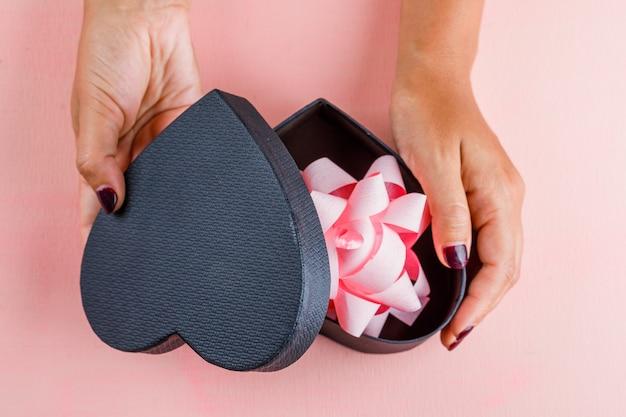 Concept de célébration sur table rose à plat. femme ouvrant la boîte-cadeau.